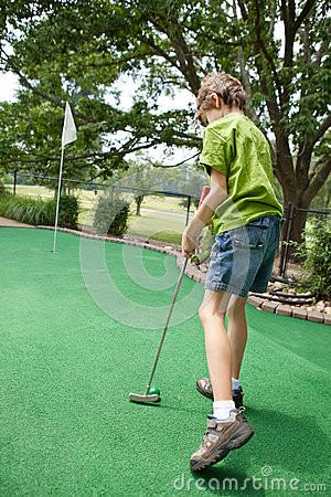 criança-que-joga-o-mini-golfe-30625070.jpg